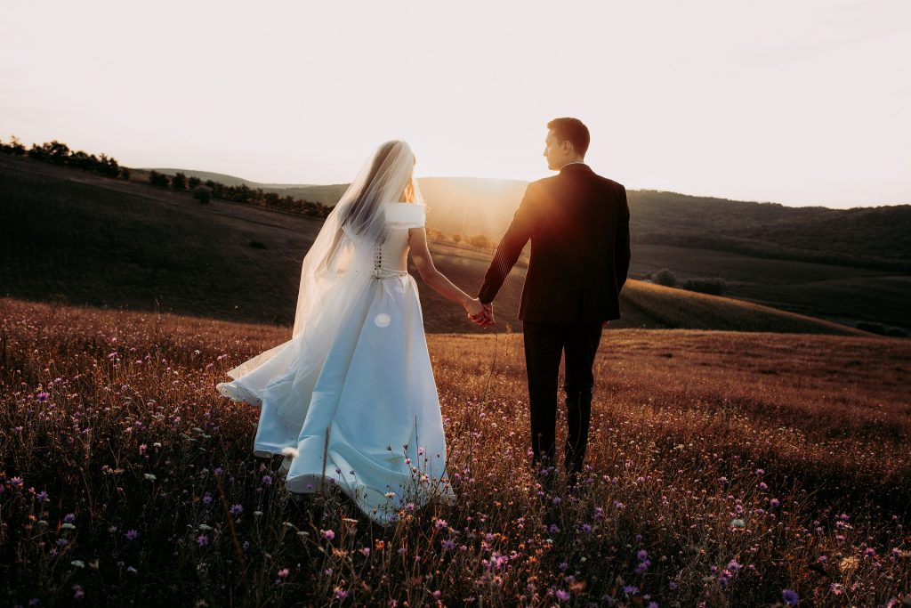 bride and groom walking in the sunset